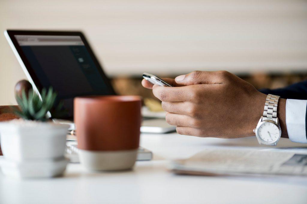 Como importar Material de Escritório da China Homem mexendo no celular em mesa de trabalho