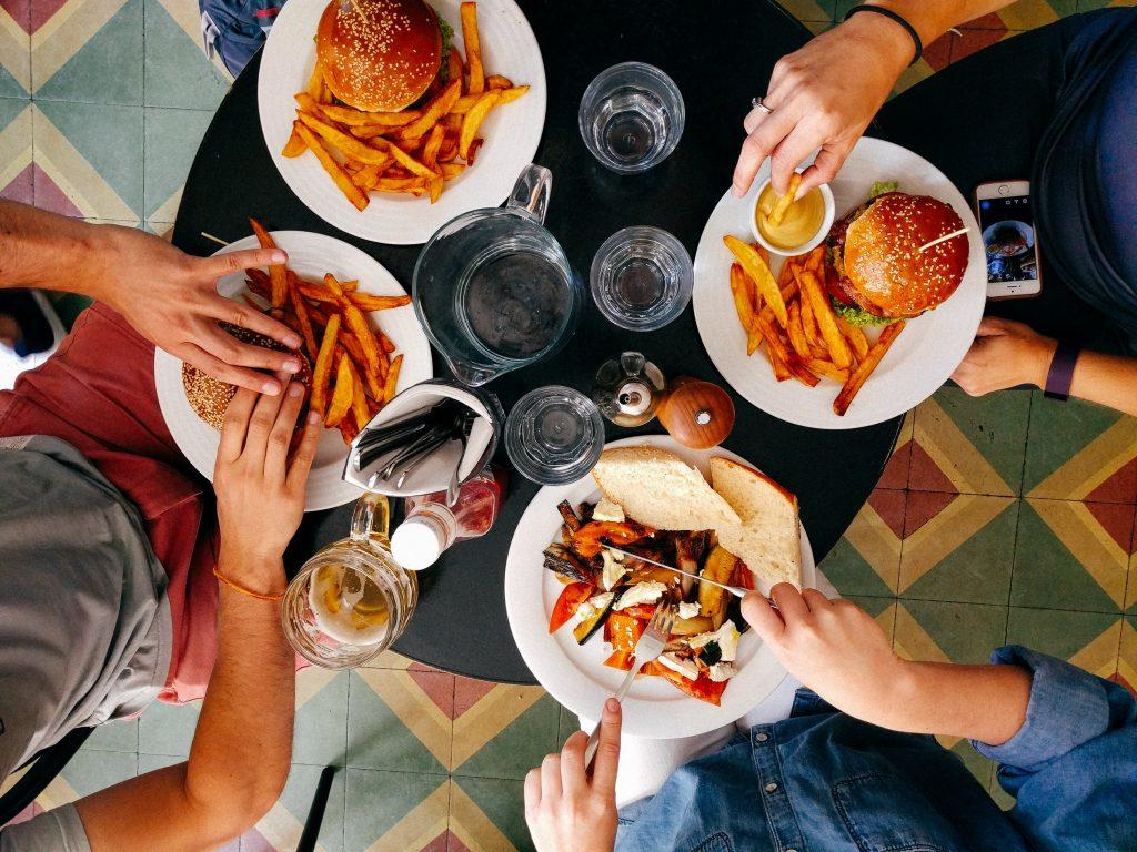 Como importar produtos Alimentícios e Nativos da China Quatro pessoas comendo hambúrguer e batata frita