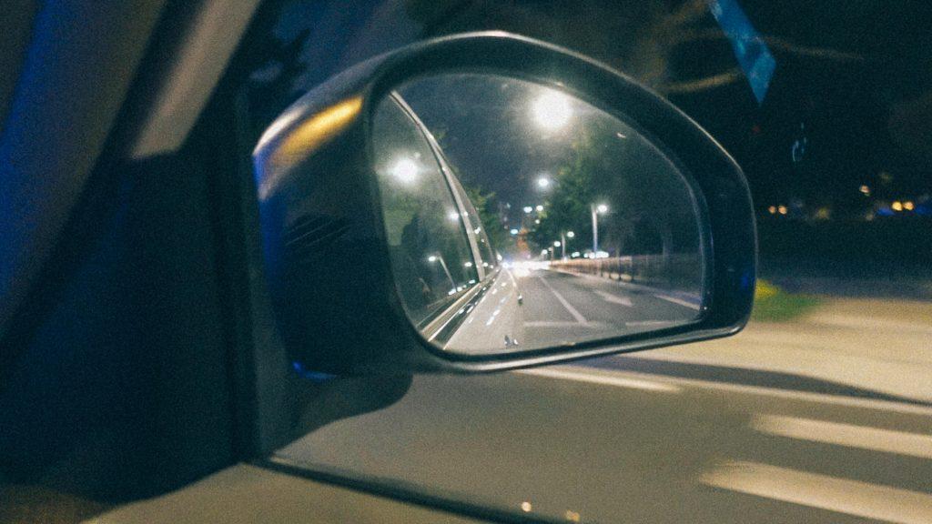 Como se ferrar com importação em 3 passos infalíveis Imagem de rua pelo retrovisor de um carro